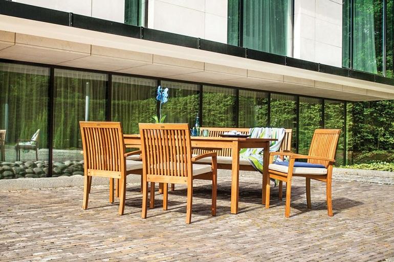 Komplet krzeseł z drewna akacjowego przy obiadowym stole na tarasie fot. Ogrodosfera.pl